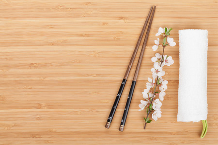 kitchen table top: Chopsticks and sakura branch over bamboo table with copy space