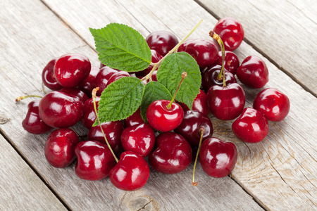 Ripe cherries on wooden table with green leaves
