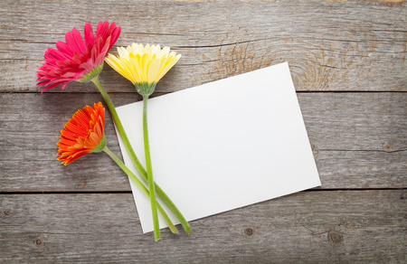 Gerbera: Three colorful gerbera flowers and blank greeting card on wooden table