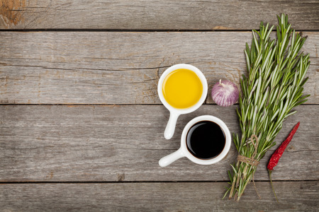 Olive oil and vinegar with spices over wooden table background with copy space Stock Photo