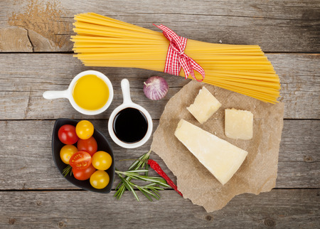 Parmesan cheese, pasta, tomatoes, herbs and spices on wooden table background photo