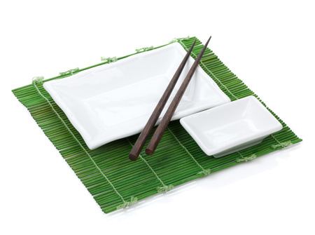 Empty plate and chopsticks over mat. Isolated on white background