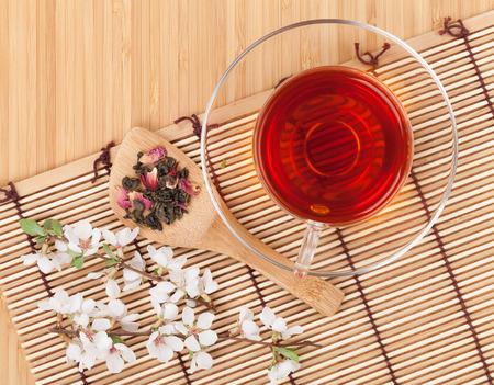 Japanese green tea and sakura branch over mat and bamboo table photo
