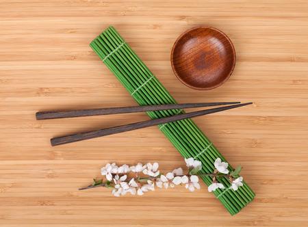 Chopsticks and sakura branch over bamboo mat  photo
