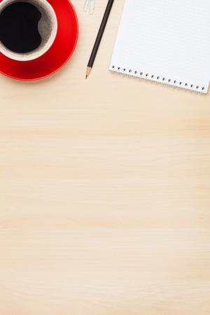 メモ帳とコーヒーのカップとのオフィスのテーブル。コピー領域の上からの眺め 写真素材