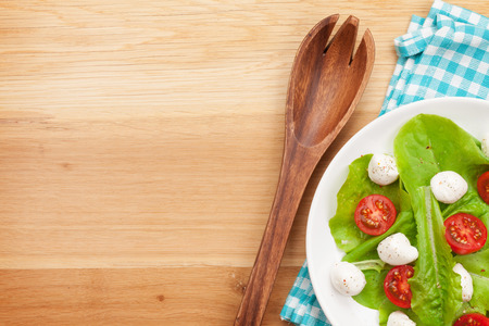 Fresh healthy salad on wooden table with kitchen utensil photo
