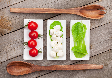 Tomatoes, mozzarella and green salad leaves on wooden table background photo