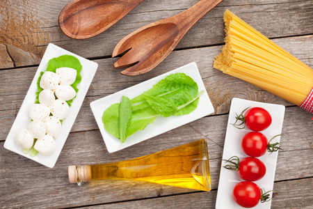 Tomatoes, mozzarella, pasta and green salad leaves on wooden table background photo