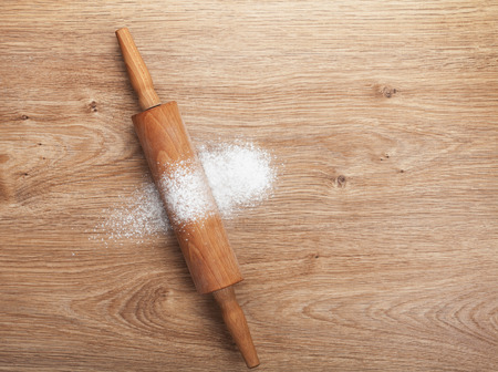 Rolling pin with flour on wooden table. View from above photo