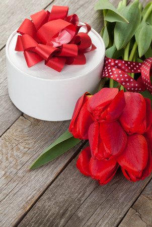 Fresh red tulips with gift box over wooden background photo