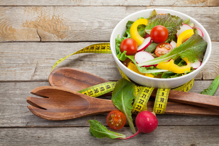eating utensil: Fresh healthy salad, utensil and measure tape on wooden table background Stock Photo
