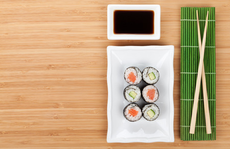 Sushi set, chopsticks and soy sauce over bamboo table with copy space photo