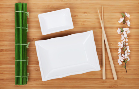 Empty plates, chopsticks and sakura branch over bamboo table photo