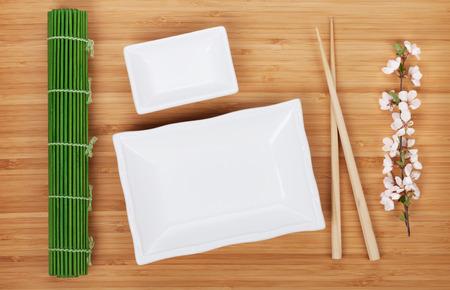 Empty plates, chopsticks and sakura branch over bamboo table photo