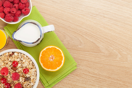 cereal: Healty breakfast with muesli, berries and orange juice. View from above on wooden table with copy space
