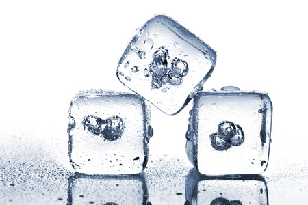 Three melting ice cubes with water dew on white background photo