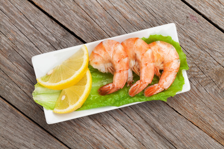 tiger shrimp: Cooked shrimps with lemon. View from above on wooden table