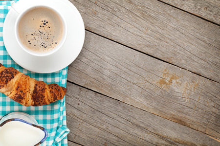 Cup of coffee, milk and fresh croissant on wooden table with copy space photo