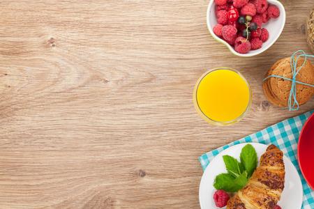 petit déjeuner: Petit healty avec du muesli, fruits, jus d'orange, café et un croissant. Vue de dessus sur la table en bois, avec copie espace