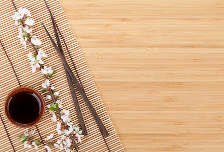 Chopsticks and sakura branch over bamboo mat with copy space photo