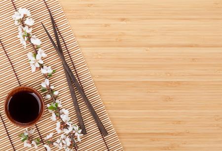 Eetstokjes en sakura tak over bamboe mat met kopie ruimte