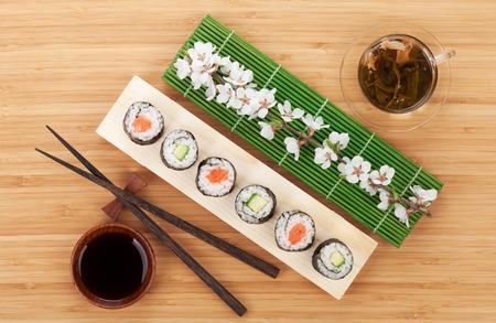 maki: Sushi set with green tea and sakura branch on bamboo table Stock Photo