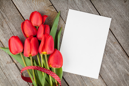 space for copy: Fresh tulips bouquet and blank card for copy space over wooden table background