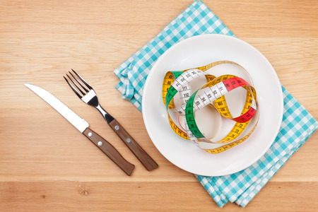 Plate with measure tape, knife and fork. Diet food on wooden table photo