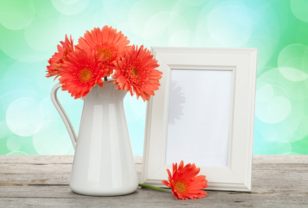 Orange gerbera flowers and photo frame on wooden table with sunny bokeh background photo
