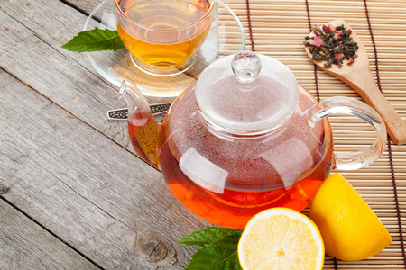 yellow tea pot: Green tea with lemon and mint on wooden table. Closeup with copy space