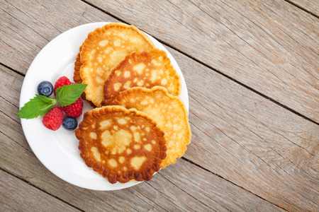 Pancakes with raspberry, blueberry and mint. On wooden table with copy space photo