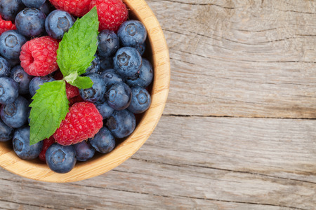 Blueberries and raspberries with mint leaf on wooden table with copy space photo