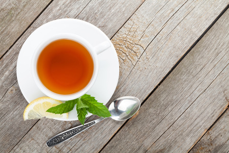 cup of tea: Green tea with lemon and mint on wooden table background with copy space