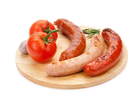 Various grilled sausages and tomatoes on cutting board. Isolated on white background photo