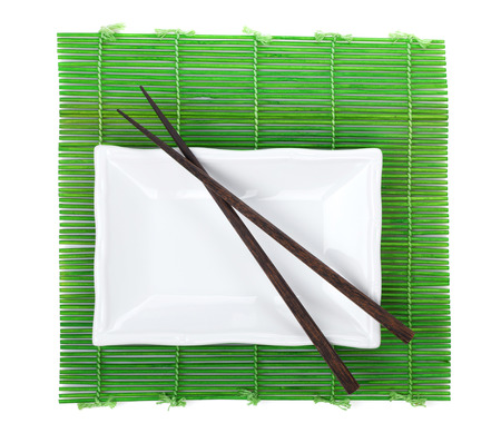 Chopsticks and utensils over bamboo mat. Isolated on white background photo