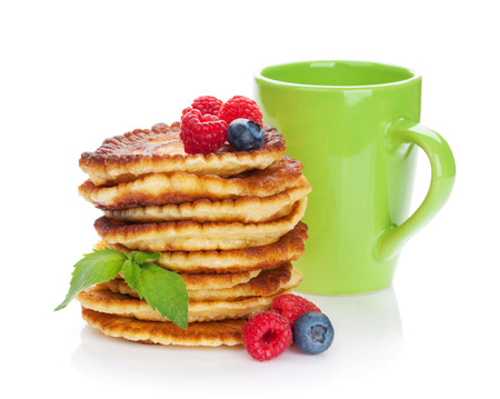 Pancakes with raspberry, blueberry and cup of drink. Isolated on white background photo