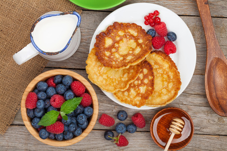 Pancakes with raspberry, blueberry, mint and honey syrup. On wooden table photo