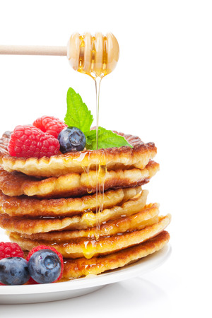 Pancakes with raspberry, blueberry, mint and honey syrup. Isolated on white background photo