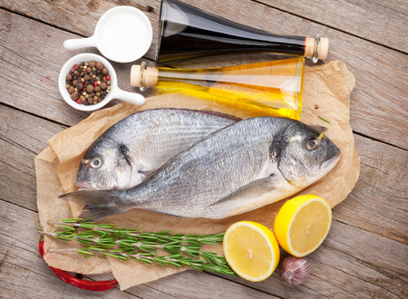 gilthead: Fresh dorado fish cooking with spices and condiments on wooden table Stock Photo