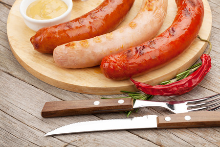 Various grilled sausages with condiments on cutting board photo