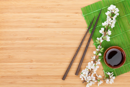 kitchen table top: Chopsticks, sakura branch, soy sauce and bamboo mat on wooden table with copy space Stock Photo
