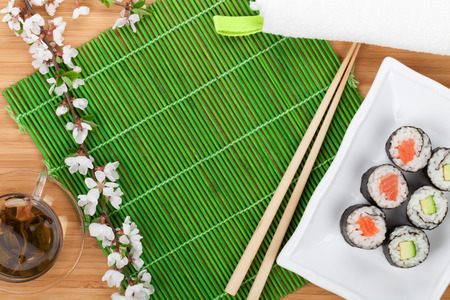 Sushi set, chopsticks and sakura branch over bamboo table with copy space photo