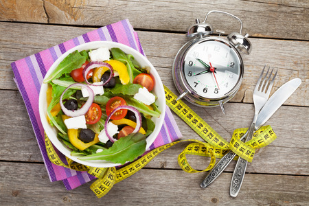 Fresh healthy salad and measuring tape on wooden table. Healthy food