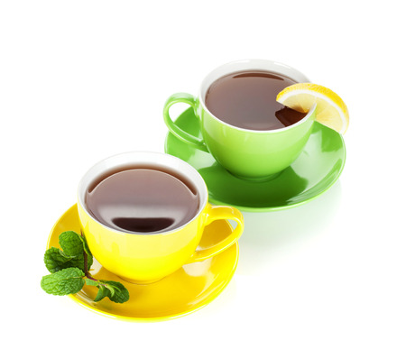 Two colorful cups of tea with lemon and mint. Isolated on white background photo