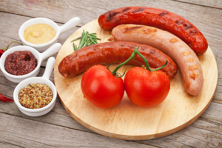 Various grilled sausages with condiments and tomatoes on cutting board photo