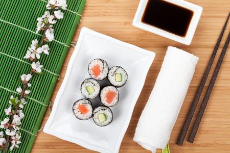 Sushi maki set with fresh sakura branch over bamboo table photo