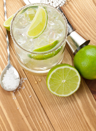 cocktail strainer: Classic margarita cocktail with salty rim on wooden table with limes and drink utensils Stock Photo
