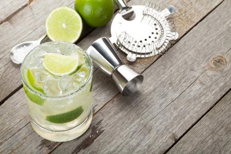 coctel margarita: Cóctel clásico margarita con borde salado en mesa de madera con limones y utensilios de bebida