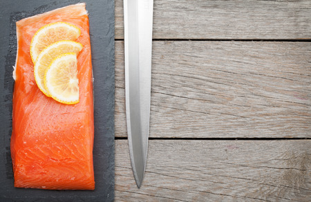 Fresh salmon fish with lemon and japan knife on wooden table with copy space photo