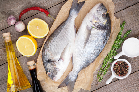 sea bass: Fresh dorado fish cooking with spices and condiments on wooden table Stock Photo
